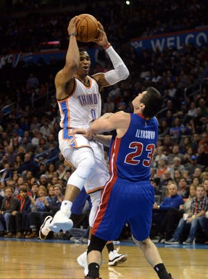 Nov 27, 2015; Oklahoma City Thunder guard Russell Westbrook (0) commits a charging foul against Detroit Pistons forward Ersan Ilyasova (23) during the fourth quarter at Chesapeake Energy Arena.