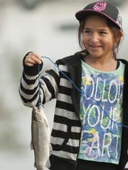 Madison Gonzalez, 8, holds a fish caught during the Visalia Parks and Recreation's annual fishing derby.