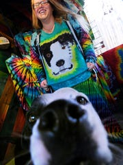 Corrie Wolfe laughs as she shows off her custom tie-dyed shirt depicting her dog, Watson. Wolfe opened her Howlin' Dyes clothing store at Play Faire Park in September.
