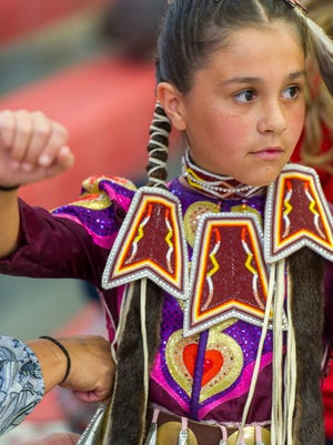 Wunupehaee Leslie adjusts her costume before her performance at the Native American powwow in the Paiute Tribal Clinic Friday, March 30, 2018. American Indians from across the West gathered to dance, share traditional foods, and listen to drum songs.