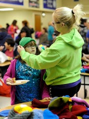 Desiree Maxwell helps her daughter, Grace Maxwell, 7, try a hat on during the Chillicothe City School District's Community Day on Tuesday. Families of students were invited to come to the school to get a free tote bag, canned goods, books, hat, gloves, dinner, haircut, picture with Santa and more.