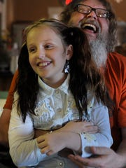 Emi Sunshine Hamilton, 10, laughs with her father and bandmate, Randall, during a band meeting on Monday, Nov. 10, 2014, in Madisonville, Tenn.