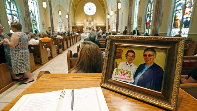 A photograph of Sister Margaret Held, left, and Sister Paula Merrill is placed at the entrance to the Cathedral of St. Peter the Apostle on Monday in Jackson, where a memorial Mass was held for the two 68-year-old nuns who were killed last week in their Durant home.
