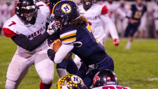 Northern's Theo Ellis is taken down by players from Roseville High School during the MHSAA Division 2 playoff game at Memorial Stadium Oct. 27.