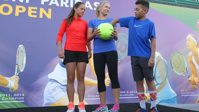 Brodie Young-Smith pulls Serena Williams name for the first draw at the BNP Parbias Open in Indian Wells, March 7, 2016.   The players helping with the draw are Daria Kasatkina, left, and Daria Gavrilova, center.