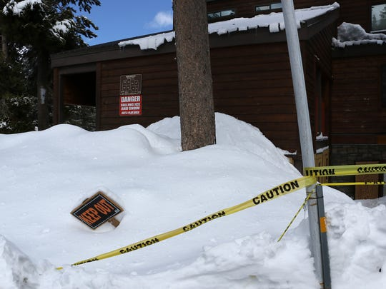 Caution tape and signs are seen urging people not to walk under snow laden rooftops at the Edelweiss complex at Kirkwood Mountain Resort in California on March 23, 2018.