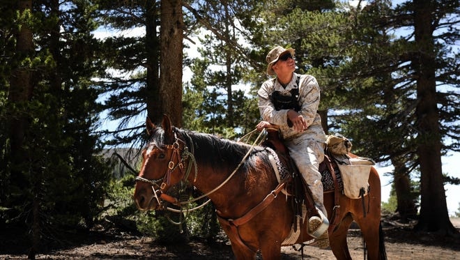 Marine Staff Sgt. John Freeseha rides along a trail during training to be combat-ready on horseback.
