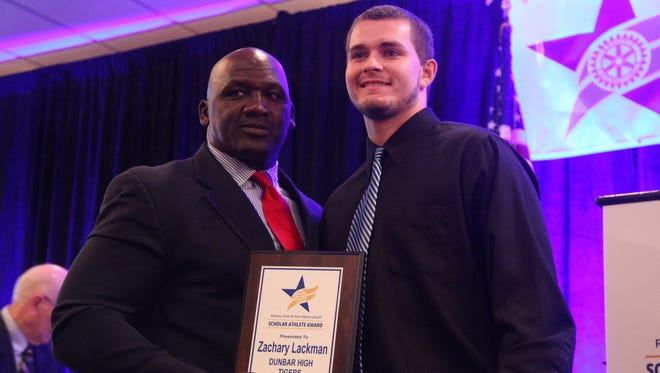 Dunbar High School's Zachary Lackman receives his award from former NFL runningback Albert Bentley during the 30th Annual Rotary South Scholar Athlete Banquet on Wednesday.