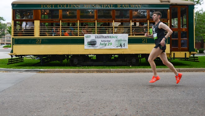 "A runner passes by the trolley from the Fort Collins Municipal Railway as he warms up for the start of the Human Race 5K on Mountain Avenue on Saturday, July 29, 2017. Runners are challenged to ""beat the trolley"" as it travels along the course of the race."