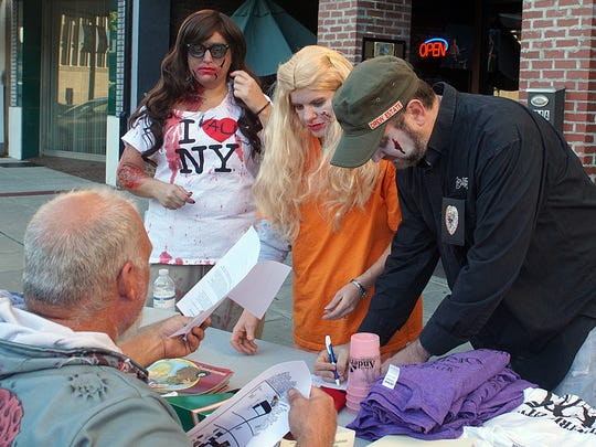 Zombies sign up for the Zombie Pub Crawl in downtown Anderson.