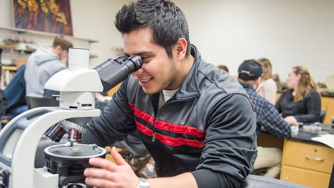 UW-River Falls student Leonel Turcios, a geology major from Minneapolis, uses one of the new microscopes purchased by the Stone Geology Fund.