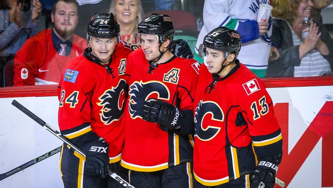 Calgary Flames defenseman Kris Russell (4) celebrates his goal with wingers Jiri Hudler (24) and Johnny Gaudreau (13) against the Vancouver Canucks during the preseason.