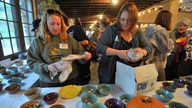 In this 2013 file photo, volunteers Donnell Schubring, left, and Jolene Zannino, both of Wausau, distribute bowls on a table during the Empty Bowls fundraiser at the Rothschild Pavilion.