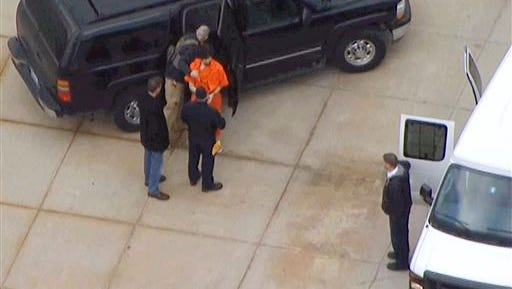 In this still images from aerial video provided by WHDH-TV in Boston, Boston Marathon bombing suspect Dzhokhar Tsarnaev, center wearing an orange jumpsuit, is transferred between vehicles in Devins, Mass., following his hearing in federal court Thursday in Boston. Tsarnaev is charged with carrying out the April 2013 attack that killed three people and injured more than 260. He could face the death penalty if convicted.