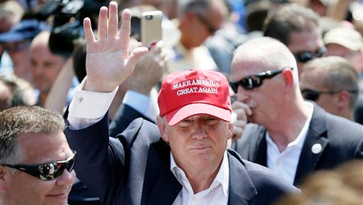Republican presidential candidate Donald Trump waves to fairgoers as he walks down the concourse during a visit to the Iowa State Fair, Saturday, Aug. 15, 2015, in Des Moines, Iowa. (AP Photo/Charlie Neibergall)