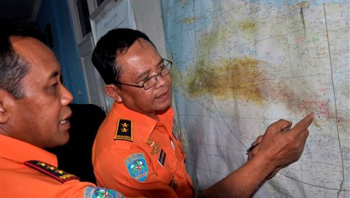 National Search And Rescue Agency (BASARNAS) chief F. Henry Bambang Soelistyo, left, looks at a map with Air Vice Marshal Sudipo Handoyo during a search operation for the missing Trigana Air Service flight at Sentani airport in Jayapura, Papua province, Indonesia, Monday, Aug. 17, 2015. Rescuers are making their way into the rugged mountains of Indonesia's easternmost province of Papua, where the airliner carrying 54 people went missing in bad weather Sunday. (AP Photo/Alfian)