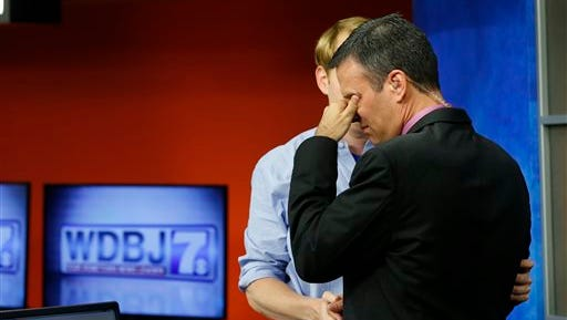 WDBJ-TV7 anchor Chris Hurst, left, comforts meteorologist Leo Hirsbrunner during the early morning newscast at the station, in Roanoke, Va., Thursday, Aug. 27, 2015. Hurst was the fiance of Alison Parker, who was killed during a live broadcast Wednesday, in Moneta. (AP Photo/Steve Helber)