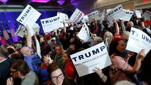 Supporters for Republican presidential candidate Donald Trump hold signs during a South Carolina Republican primary night event Saturday, Feb. 20, 2016, in Spartanburg, S.C. (AP Photo/Paul Sancya)