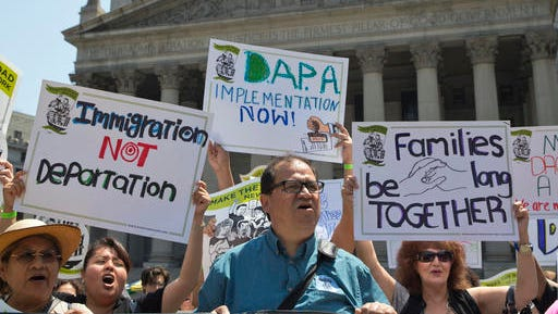FILE - In this June 24, 2016, file photo, demonstrators protest against a Supreme Court decision on immigration outside the New York Supreme court in New York. The future of millions of people living in the U.S. illegally could well be shaped by the presidential election. The stakes are high, too, for those who employ them, help them fit into neighborhoods, or want them gone. (AP Photo/Mary Altaffer, File)