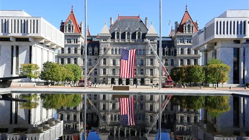 The state Capitol is reflected in a fountain before a ceremony at the New York State Fallen Firefighters Memorial on Tuesday, Oct. 6, 2015, in Albany, N.Y.