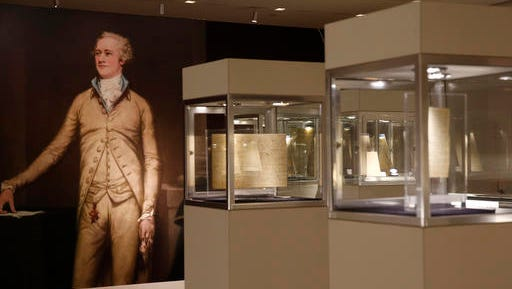 Letters penned by or pertaining to Alexander Hamilton, left, in a painting, are displayed in cases, Tuesday, Jan. 10, 2017, at Sotheby's in New York. The documents and artifacts, which include love letters to his wife Eliza, will be offered up for auction at Sotheby's on Jan. 18.