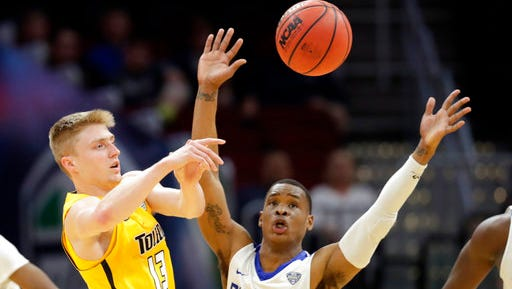 Toledo's Jaelan Sanford, left, passes against Buffalo's Davonta Jordan during the first half of an NCAA college basketball championship game of the Mid-American Conference tournament, Saturday, March 10, 2018, in Cleveland.