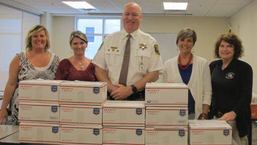 Sheriff Tim Donnellon with the finished boxes to be sent to the troops, with (left to right) Molly McIntyre, Karen Doherty, Andrea Blair and Linda Palazzolo, who packed the boxes.