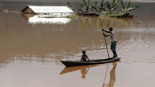 An Indian villager paddles a boat through floodwaters past a partially-submerged house in Balbala village,  near  the capital of the northeastern state of Assam on Wednesday, Sept. 24, 2014.