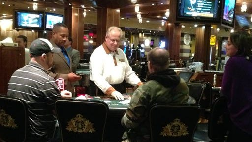 A dealer deals the final hand of blackjack at Trump Plaza Hotel and Casino in Atlantic City, N.J., seconds before the casino closed on Tuesday, Sept. 16, 2014. Trump Plaza is the fourth Atlantic City casino to go out of business so far this year. (AP Photo/Wayne Parry)