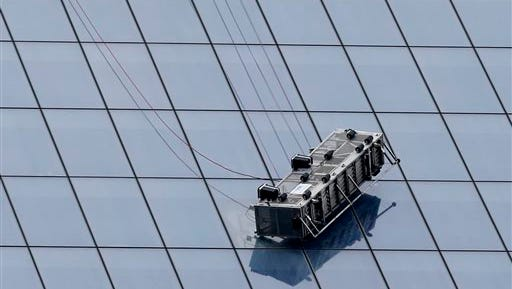 A partially collapsed scaffolding hangs from the 1 World Trade Center in New York, Wednesday, Nov. 12, 2014. New York City firefighters have been called to the nation's tallest skyscraper, where two workers are stuck on scaffolding 69 stories above street level. (AP Photo/Kathy Willens)