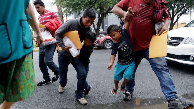 Young immigrants are lifted over a puddle as they arrive with their parents at the Catholic Charities RGV after they were processed and released by U.S. Customs and Border Protection.