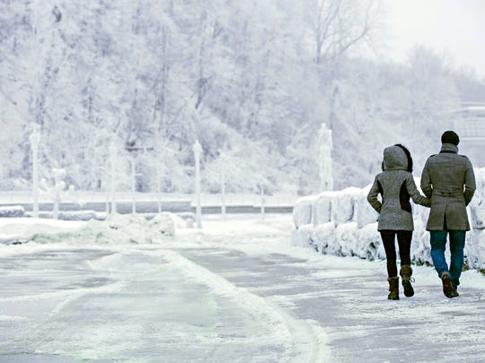 A couple walks near the brink of the Horseshoe Falls in Niagara Falls, Ontario, as cold weather continues through much of the province on Friday, Dec. 29, 2017. (Aaron Lynett/The Canadian Press via AP)