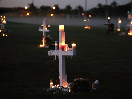 PARKLAND, FL - FEBRUARY 17: Candles glow at a memorial site to honor 17 people who were killed in the February 14 shooting at Marjory Stoneman Douglas High School, on February 17, 2018 in Parkland, Florida. Former student Nikolas Cruz has been arrested and charged for the 17 murders.