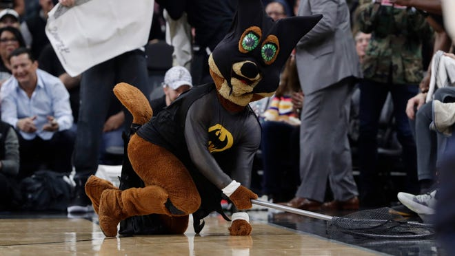 San Antonio Spurs mascot, The Coyote, uses a net as he dives for and catches a bat during the first half of an NBA basketball game between the San Antonio Spurs and the New Orleans Pelicans in San Antonio, Saturday, Feb. 2.
