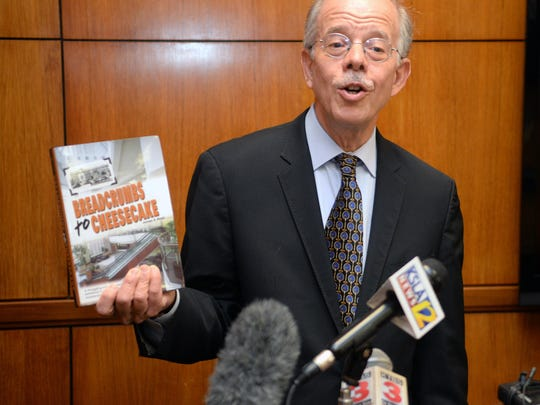 """David Ettinger, attorney for Biomedical Research Foundation and Vantage Health Plan, holds up James Elrod's book """"Breadcrumbs to Cheesecake"""" while discussing the antitrust lawsuit filed against Willis-Knighton Health System. Elrod is the Willis-Knighton CEO."""