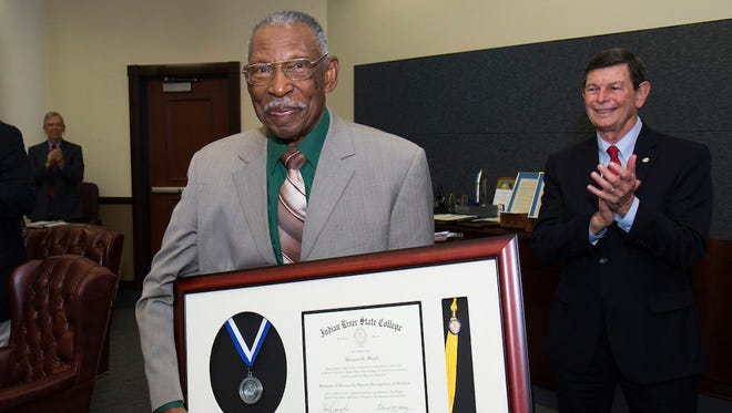 Vernon H. Floyd received an honorary diploma from Indian River State College at the Nov. 28 IRSC District Board of Trustees meeting in honor of his life-long commitment to higher education and to the community.IRSC President Dr. Edwin R. Massey is pictured in the background.