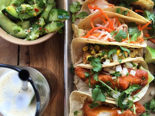 Cucumber salad, iced tea and a selection of tacos at