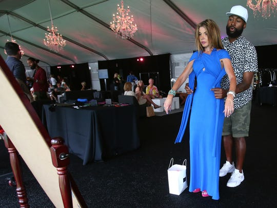 Mychael Knight styles one of his scarf dresses on Shelley Wegner of Canada during a trunk show featuring Project Runway designers as part of Fashion Week El Paseo on Wednesday, April 6, 2016, in Palm Desert, Calif.