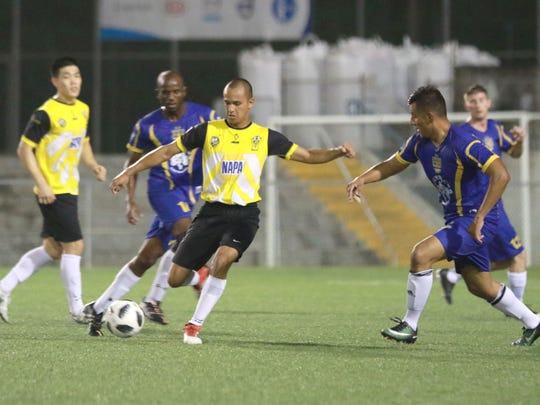 NAPA Rovers FC's Matt Robles prepares to pass the ball as Bombers SC defenders begin to converge on him in a semifinal match of the Jamaican Grill 11th Annual GFA Cup at the Guam Football Association National Training Center on June 23. The Rovers won 10-1.