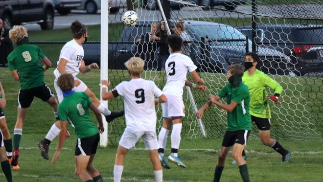 Zeeland East's Brayden Tuffs, far left, heads the ball into the net past Zeeland West keeper Isaiah Cifuentes in the second half Tuesday at Zeeland West.