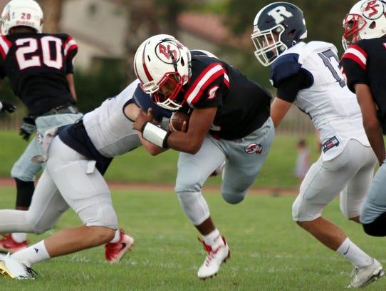 Palm Springs' quarterback Jeremy Dotson carries the