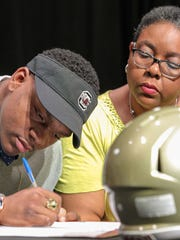 Pendleton High School senior Brad Johnson, left, signs a letter of intent to play for the University of South Carolina football team, on Wednesday, February 1, during an assembly of students, teammates, family, and friends at the school in Pendleton.