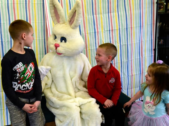 "Parker Boss, 7, left, and his siblings Grady, 5, and Caralyn, 3, of Elmore meet the Easter Bunny during Oak Harbor High School Student Council's ""Easter Eggstravaganza."""