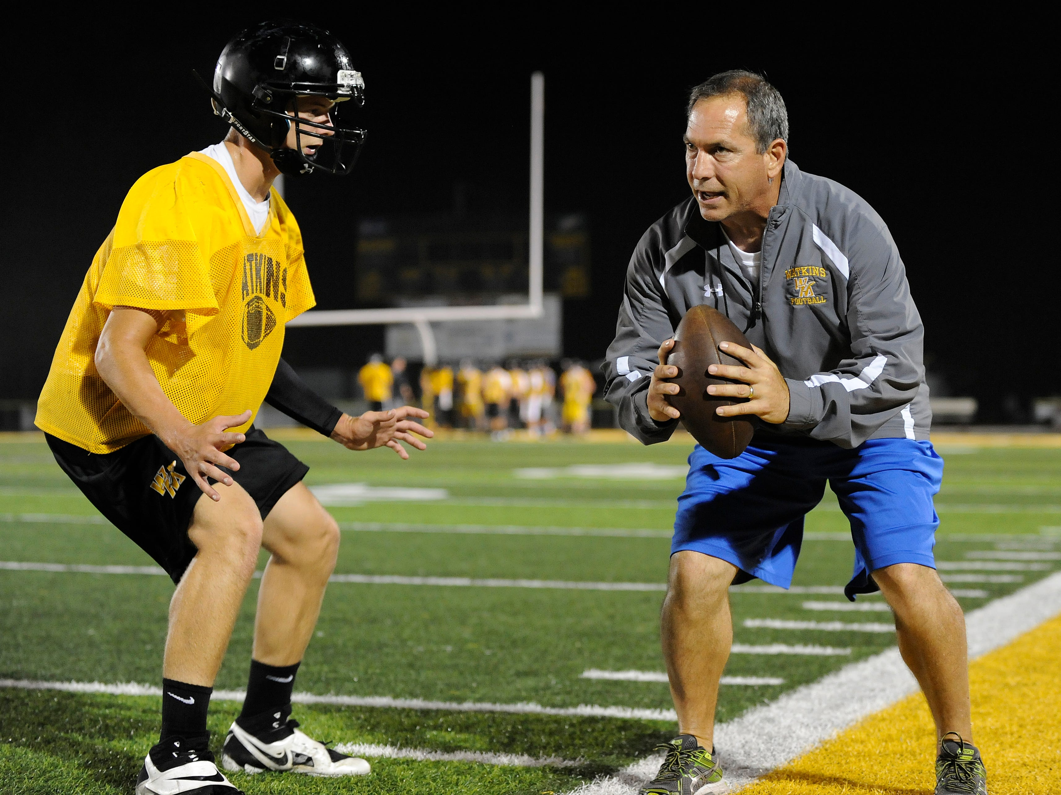 Watkins Memorial football coach Jeff Severino, right, runs Cole Nixon through a secondary drill during the Warriors' midnight practice this past August. Severino said the Warriors are operating as usual in advance of the upcoming vote on the critical renewal levy.