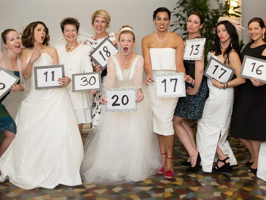 Charlene Couillard, sixth from left, renewed her wedding vows on Saturday at the Hotel Indigo in downtown Fort Myers. Couillard asked her married friends to join her and wear their wedding dresses. Couillard was celebrating 20 years of marriage to Craig Couillard. The signs indicate years of marriage.