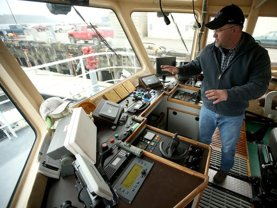 Deckhand Jason Moosmiller gives a tour of the bridge of the Navy tugboat Manhattan at Naval Base Kitsap Bremerton.