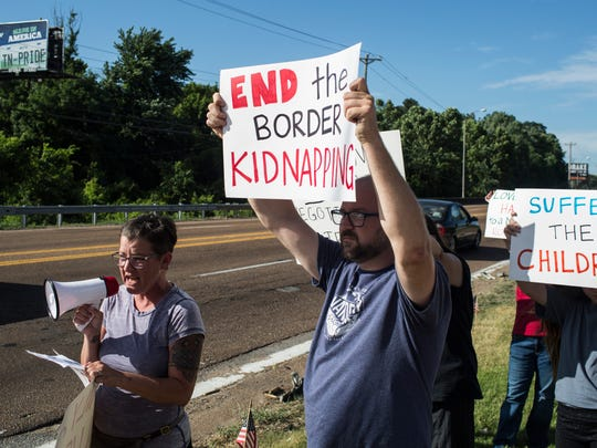 Lorin Vincent, left, speaks through a megaphone while others hold signs along Summer Avenue near a federal immigration facility to protest the separation of children from parents.