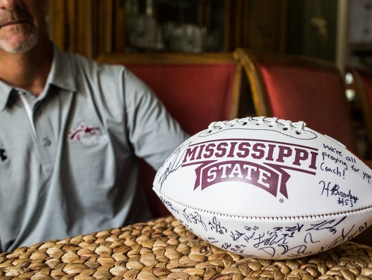 July 05, 2018 - Collierville head football coach Mike O'Neill with a signed Mississippi State football from one of his former players, Hunter Bradley. While Bradley fought past football injuries O'Neill fought cancer. O'Neill is now completely in remission and Bradley has been drafted by the Green Bay Packers.