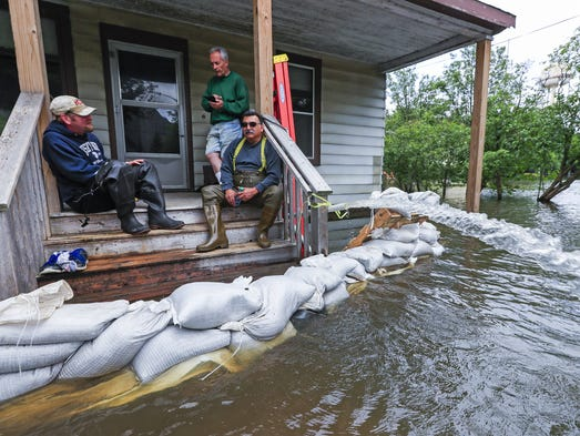 Gary Campbell, center, stands on the porch of his sand-bagged