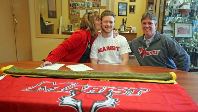 Donna Breit kisses her son, Connor Breit, a Nanuet senior who just signed with Marist on National Signing Day with her husband, Raymond Breit at Nanuet High School on Feb. 1, 2017.
